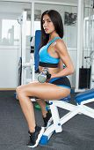 Active woman in sportswear sitting sideways and engaged with dumbbells in the gym. Legs apart. Sports nutrition. Shiny skin. Beautiful body. fitness poster