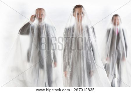 Trapped business team covered in plastic standing at office.creative conceptual photo showing that people become trapped in their jobs and careers that takes up all their time