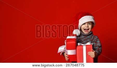 Funny Smiling Joyful  Child Boy In Santa Red Hat Holding Christmas Gift In Hand Over The Red Backgro