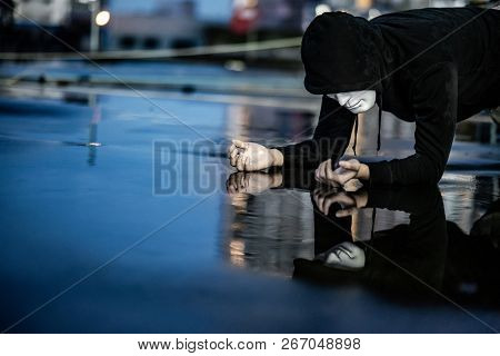 Reflection Of Mystery Hoodie Man In White Mask Feeling Guilty Looking His Face On Wet Floor After Th