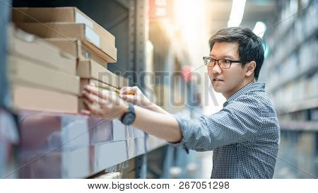 Young Asian man worker using tape measure for measuring dimension of product in cardboard box. Shopping lifestyle in warehouse concept poster