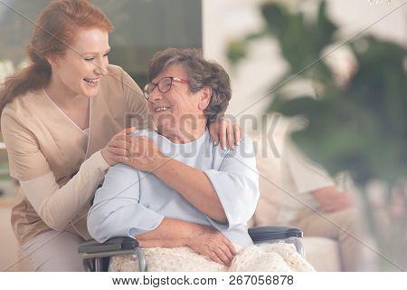 Smiling Nurse Helping Happy Senior Woman In The Wheelchair
