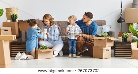 Happy Family Mother Father And Children Move To A New Apartment And Unpack Boxes