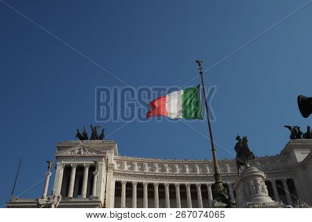 Altare Della Patria Or Monument Nazionale, Rome, Italy, With The Italian Flag Flying In Front Of A B