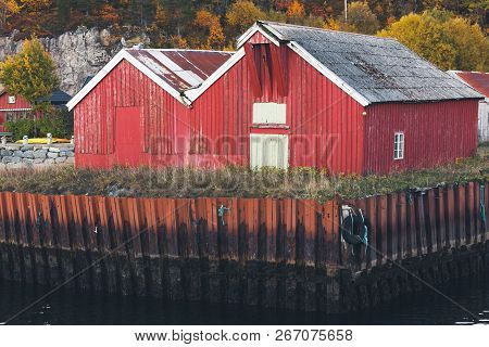 Traditional Red Wooden Barns Stand On Seacoast In Norway. Rural Norwegian Landscape At Autumn Day
