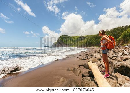 Travel tourist woman in Hawaii beach USA vacation on Pololu Valley hike to beach looking at ocean landscape mountains background. Big Island, Hawaii. Girl hiking with backpack in summer holidays.