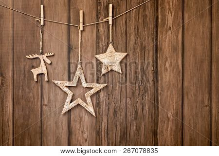 Rustic Christmas Ornaments Hanging With String On Wood Backdrop