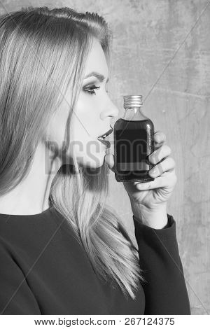 Girl Posing With Bottle Of Red Liqueur. Pretty Woman With Blond Long Hair And Fashionable Make Up In