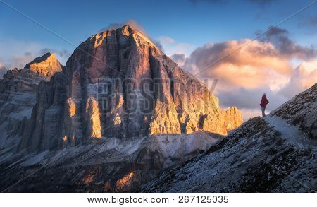 Woman On The Trail Looking On High Mountain Peak At Sunset