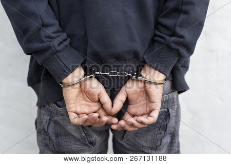 Criminal Under Arrest Confined With Handcuffs And Hands At His Back, Standing Next To A Wall