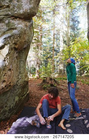A Man Rock Climber Is Preparing To Climb A Rock And His Partner Watching A Rock.