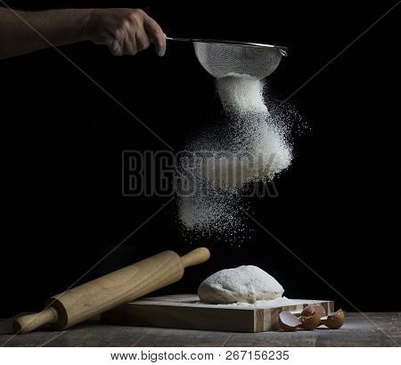 Flour Is Sprinkled Over A Ball Of Dough On A Wooden Board With Roller And Eggs