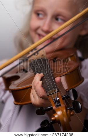 Cute Little Girl In A Bright Blouse Plays The Violin Close-up On A Gray Background