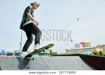 Full length portrait of contemporary young man doing longboard stunts on ramp in skateboarding park, copy space poster