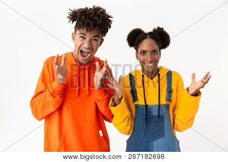 Portrait of a two confused young african couple isolated over white background, shrugging shoulders