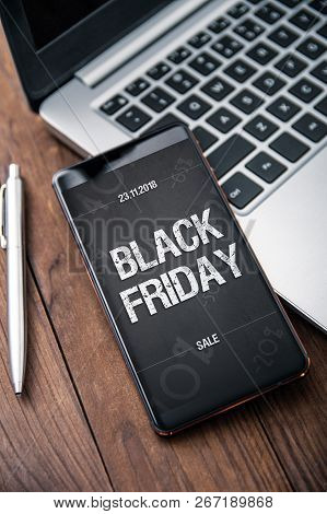 Modern Smartphone With Black Friday Banner On The Screen Lies On Wooden Desk. Application On Screen