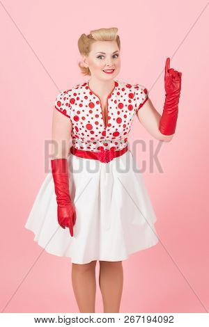 Emotional Pretty Lady Dressed In Pin Up Style Feeling Interested And Pointing Her Finger Up While Th