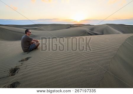 Man Sitting And Relaxing On Sand Dunes By The Sunrise, In Maspalomas On Gran Canaria.