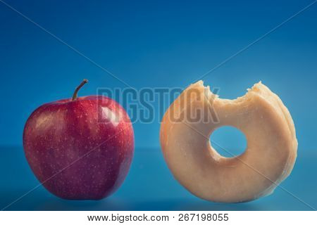 Bitten Donut And Whole Red Apple. Diet Concept Photography.