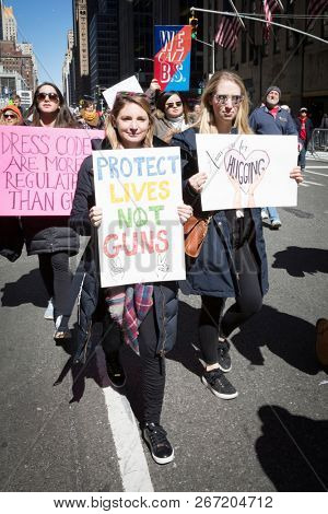 March For Our Lives: Participants in the march to end gun violence hold signs with various phrases including Protect Lives Not Guns, on 6th Ave, NEW YORK MAR 24 2018.