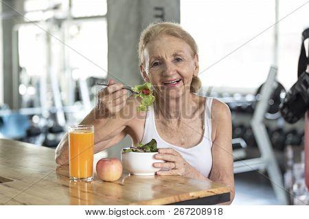Senior Woman Eating Healthy Salad And Orange Juice. Elderly Health Lifestyle Concept.