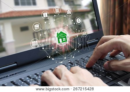 Hand Use Laptop Computer With Property Investment Icons Over The Network Connection On Property Back