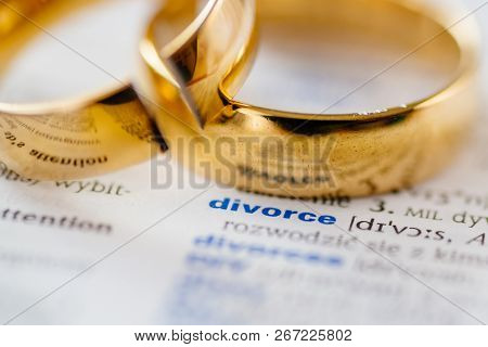 Two Broken Wedding Rings On Divorce Word In Dictionary.