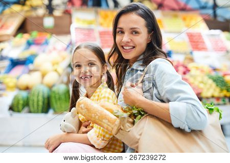 Cheerful beautiful family doing shopping at farmers market: smiling attractive mom with bag full of fresh product embracing cute daughter and looking at camera