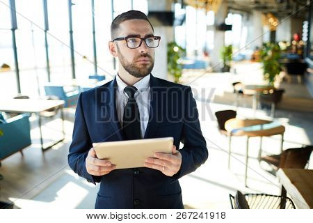 Young pensive owner of cafe in formalwear and eyeglasses searching in the net for some recommendations about menu or interior