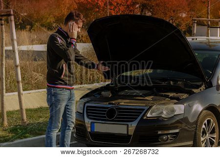 A Young Man Is Standing By A Broken Car And Looks Under The Car Hood.a Young Man Is Standing By  Bro
