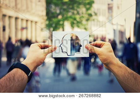 Man Hands Holding A White Paper Sheet With Two Faced Head Over A Crowded Street Background. Split Pe