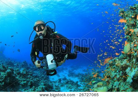 Scuba Diver photographer with SLR camera diving over a coral reef in the Red Sea