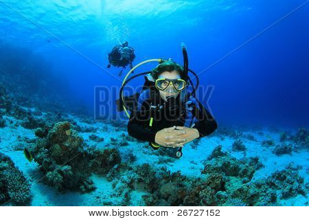 Young Woman Scuba Diving Instructor exploring a Coral Reef in the Red Sea