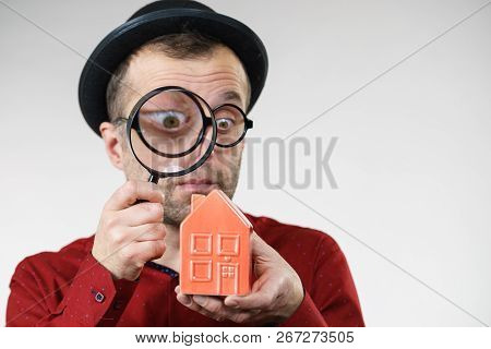 Funny Looking Adult Man Examining Red Model Home Using A Magnifying Glass, House Inspection And Real