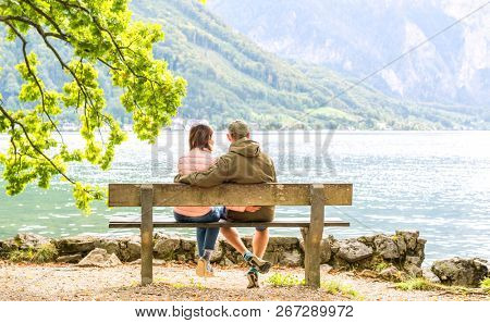 Happy couple sitting on the wooden bench and taking pleasure of amazing panoramic landscape