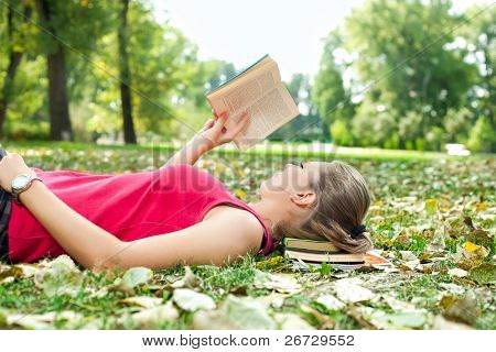 young woman relaxing and reading book