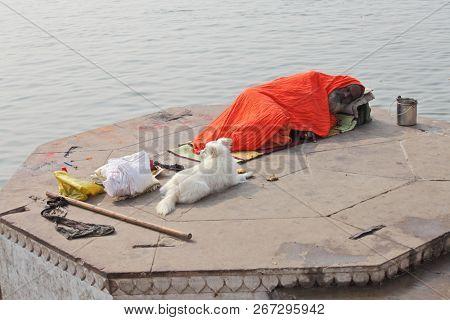 BENARES, UTTAR PRADESH, INDIA - FEBRUARY 13, 2013: Hindu sadhu is sleeping on ghat of the Ganges river