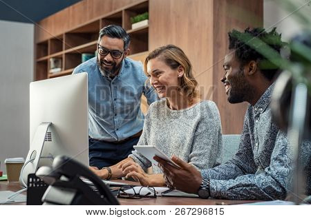 Casual businessmen and cheerful business woman in office working on a project together. Happy business man and colleagues working in a creative company. Mature businesswoman with her team working.