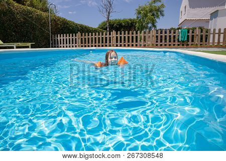 overhead shot of four years old blonde child with orange floater sleeves in arms, armbands, swimming in blue beautiful water of pool poster