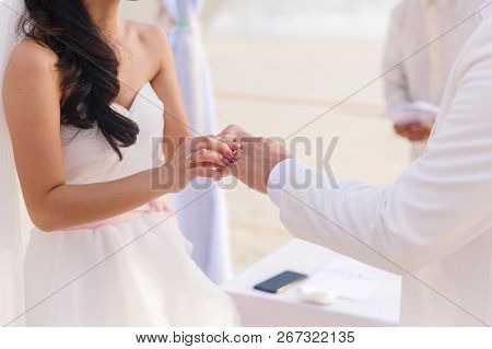 Bride Giving An Engagement Ring To Her Groom Under The Arch Decorated With Flowers On The Sandy Beac
