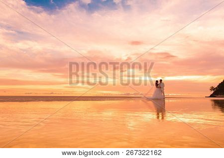 Bride And Groom With Long Veil On Tropical Beach At Sunset. Wedding And Honeymoon In The Tropics.