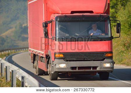 red truck driving on asphalt road in a rural landscape