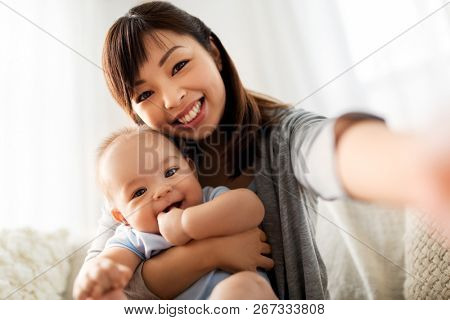 family and motherhood concept - happy young asian mother with little baby son taking selfie