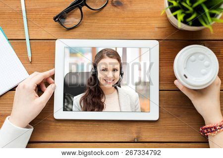 business, technology and communication concept - close up of woman having video call with customer service operator on tablet pc computer