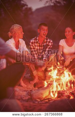 a group of happy young friends relaxing and enjoying  summer evening around campfire on the river bank