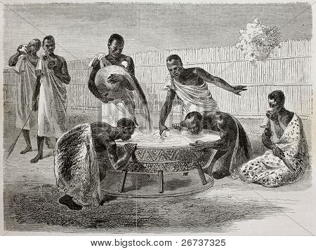 Old illustration of native Ugandan Africans drinking millet beer from a big common recipient. Created by Bayard and Dumont, published on Le Tour du Monde, Paris, 1864
