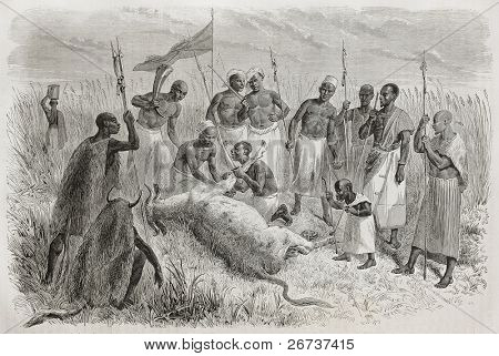 Old illustration of sorcerer performing magic rite in front of tribe members and King Kamrasi's midget, north Uganda. Created by Bayard, Trichon and Monvoisin, publ. on Le Tour du Monde, Paris, 1864