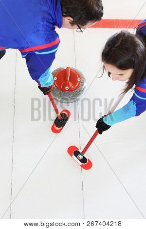 Curling, Team Playing On The Ice. Curling. Players Play Curling On The Curling Track.