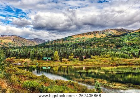 Idyllic Log Cabin By A Lake In The Mountains In The Pristine Wilderness Of Alaska During Autumn