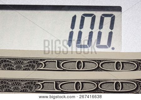 One Hundred Dollar Bills And The Number One Hundred On The Dial Of The Calculator Close-up